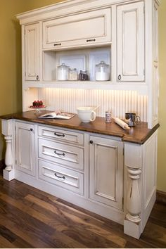 Bake center with distressed white enamel cabinets and walnut countertops