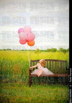 Girl, age 3 looking at balloons