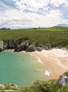 San Antonio beach seen from near Punta de San Antonio in Llanes, Asturias, Spain - a beach with crystal clear waters and surrounded by mountains covered with snow. In June! You have to see it to believe it! Come!