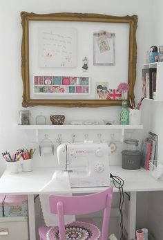 Very cute sewing nook...love the pink chair, the inspiration board/frame and the shelf with hooks for keeping it all handy.