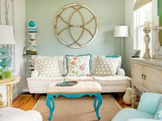 "For a small room with narrow proportions, designer Lisa Teague painted the ceiling, trim and walls one shade of white while adding a midtone color to the wall behind the sofa. ""It brings the wall a bit closer, making the room look less narrow,"" she says. ""The circular architectural detail visually helps to push the side walls out."" The paint colors, Sea Glass and Whisper, are from her collection of colors. Photography by James Salomon"