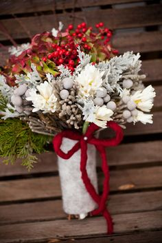 Silver brunia, dusty miller, antique green hydrangea, pepper berry, paper whites, and white hyacinthus. The bouquet was wrapped in grey wool, and red wool ribbon.