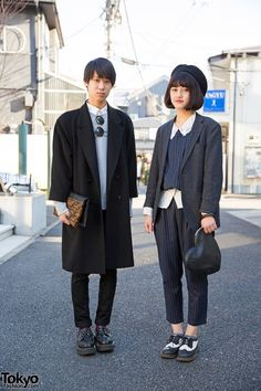 Two student on the street in Harajuku. He's wearing a resale coat over a UNIQLO items with creepers and a Freak's Store clutch. She's wearing a jacket over a matching striped top and cropped pants from Lowrys Farm, brogues, and a WEGO heart-shaped clutch