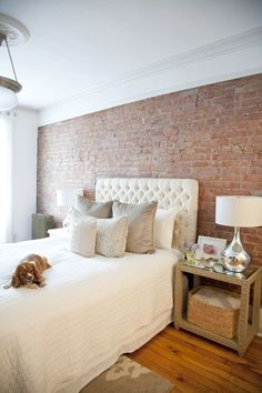 Exposed brick accent wall compliments cream shade of bedroom decor