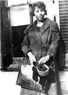 Zora Neale Hurston, outdoors, wearing overcoat, holding a hat and purse in her hand. Looking at the camera.