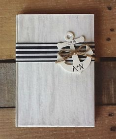 Get a regular guest book, paint it navy, then once that dries, paint it white. Take whatever ribbon you want and hot glue it on, and hot glue your decoration! TOO CUTE.