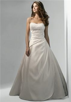 Strapless satin gown with a heavily beaded bodice, draped body with apron front skirt, and chapel train.