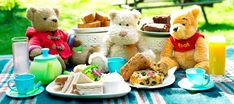 Simple buffet table ideas-- some teddy bears, some picnic items and plates of food.