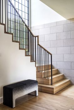Industrial stairs in modern home's hallway with cement brick walls