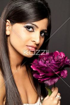 portrait of a attractive young female with fake flower. - Portrait image of a beautiful young woman with fake flower over dark background. Model: Stephanie Reddy