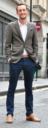 kaki colored shoes, dark blue trousers, white collared button up, and a tan cover up jacket.