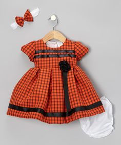 Pretty little pumpkins will feel fabulously festive dressed in this chipper set. The peppy windowpane dress boasts a lovely rose accent and comes complete with matching bloomers and a bow-topped headband.