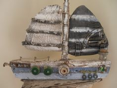 One of my driftwood boats, decorated with old jeans for the sails and a piece of chair rail for the mast. By Philippa Komercharo..