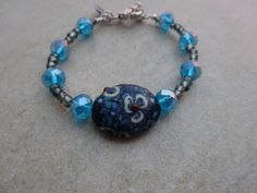 Crystal Blue and Smoke Beaded Bracelet with Floral Center Bead by MadeInTheFalls on Etsy