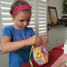 5 Surefire Tips for Sewing With Children - Threading the ribbon through the casing.  Mia came back to the project after a short break.