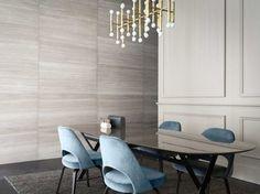 sala de jantar com pendente dourado e cadeiras azuis