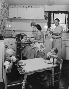 1950s mother feeds a baby seated in a high chair while the father dries his hands and smiles at their son and daughter, who are eating at a small table in a kitchen.