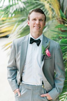 The groom is wearing a gray suit, suspenders, black bow tie and black dress shoes paired with a pink boutonniere.