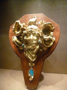 Voici l'oeuvre d'Alphonse Mucha et Adoplhe Truffier datant de 1900 : « la princesse lointaine« , une applique en bronze doré et ciselé cabochon, composée de pierres semi-précieuses, de pierre dure et de plaque d'émail. Elle fait partie de la collection du baron et de la baronne Gillion-Crowet exposée au musée fin de siècle à Bruxelles.Musee fin de siecle 031