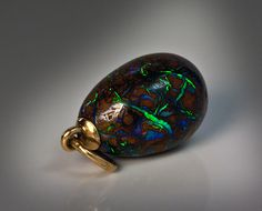 A Strikingly Beautiful Gold Mounted Carved Boulder Opal Antique Russian Miniature Egg Pendant.  This highly unusual egg was made in St. Petersburg between 1908 and 1917 by jeweler W. Warburton.  Jewelry by Warburton is extremely rare today. Clearly, this gold mounted carved egg was influenced by Warburton's neighbor - Peter Carl Faberge, whose shop was at B. Morskaia No. 16, and after 1900 - at B. Morskaia No.24.