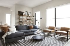 Minimal, midcentury living room featuring a dark gray sectional, round metal coffee table, family friendly area rug, and leather accent chairs Masculine Living Rooms, Living Room Grey, Rugs In Living Room, Living Room Designs, Manly Living Room, Dark Grey Sofa Living Room Ideas, Charcoal Sofa Living Room, Living Room Sectional, Gray Sectional