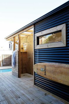 Awesome siding - tin?  Love the navy and wood together.