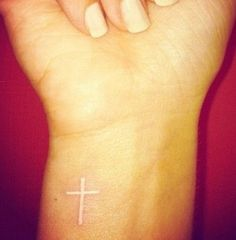 White cross wrist tattoo