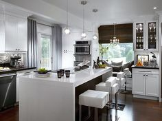 so many things to love in this kitchen! The window seat, the lighting , the gray drapes ...