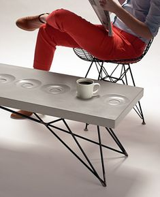A concrete coffee table with the saucers molded in. Brilliant. I'll take 2. LOL