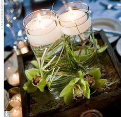 The Zen-inspired centerpieces were composed of dark wood boxes filled with sand and green cymbidium orchids. Glass cylinders in each arrangement were filled with water and a floating candle.