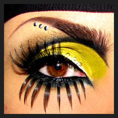 Crystals accent dramatic black and yellow eye make-up with extreme eye lashes.