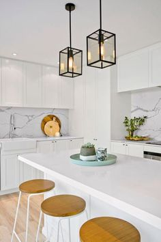 Kitchen: white Shaker cabinets, marble splashbacks, white stone benchtops, timber floorboards, wood and white bar stools, pale turquoise duck egg blue tray, two black lantern style pendant lights over island bench, farmhouse sink, chrome tapware