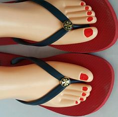 Tory Burch Thong Sandals Feature a blue thong strap adorned with her iconic logo. The footbed is red and has a large logo emblem at the heel . There are signs of street wear on the soles. Tory Burch Shoes Sandals