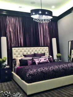 Purple bedroom. Dramatic and elegant with this backdrop wall of purple curtains, sparkling chandelier, tufted headboard and rich purple bedding .