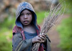 Little kid holding branches in Volcano area, Rwanda  [by Eric Lafforgue]