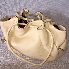 ColeHann handbag Soft sandstone leather. Two outside pockets one with a small mark (shown in picture). Magnetic closure on top. 3 interior pockets. There is some bleeding from lining onto leather also shown in picture. A few minimal ink marks on top inside bag. Bottom of bag and outside in beautiful condition, no rips or tears.  Dust bag included. Cole Haan Bags