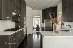 Charcoal cabinets, nickel pulls and carrera marble countertops and backsplash make this kitchen classic and modern.