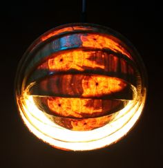 Enigmatic spherical hanging lamp looks intriguing because of the shell-like shape with warm white light inside.