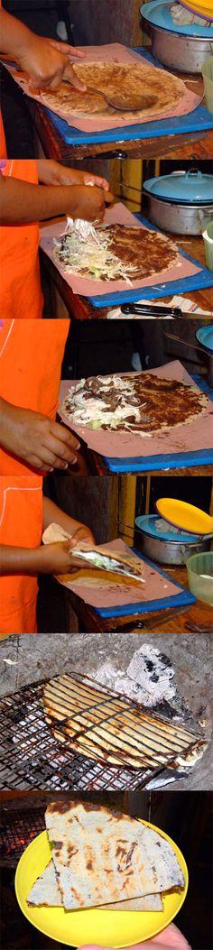 Tlayudas - comida típica de Oaxaca - Preparación tipo Quesadilla  En una tortilla de 30 cm de diámetro se unta asiento (manteca de cerdo sin refinar). Sobre el asiento untan una capa de frijoles refritos.   Después le ponen cool o lechuga, queso oaxaca deshebrado y la carne de nuestra preferencia (tasajo, bisteck, chorizo, etc).  Doblan con cuidado la tortilla y la asan a las brasas. Esto hace que la tortilla quede dorada.