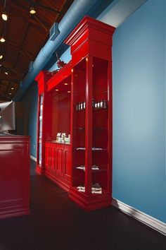 Bright red reception area with desk, shelving and a display unit