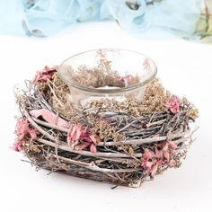 Striking candle holder, that oozes natural style Crafted from dried flowers, dusky pink petals and weaved twine, giving the impression of a natural bird;s nest. Designed with neutral colours that will compliment any preexisting décor whether it is displayed in the bedroom, bathroom or even for occasional use in the garden during the summer months Complete with Glass candle holder that is secured into a Polystyrene block making this a stable candle holder