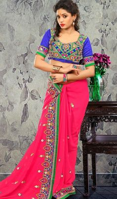 Designer fuchsia georgette sari with contrast blouse makes perfect combo for evening party requirement. The sari is garnished with lace, silk thread embroidered border, scattered embroidered appliqued floral motifs and crystal stone which gives you an elegant look. Sari comes with contrast blue raw silk stitched blouse as shown in the picture. #NewTraditionalDesignSaree