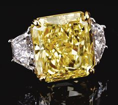 FANCY INTENSE YELLOW DIAMOND RING.  The fancy intense yellow cut-cornered rectangular modified brilliant-cut diamond weighing 21.04 carats, set between trapeze diamond shoulders, mounted in yellow gold and platinum,