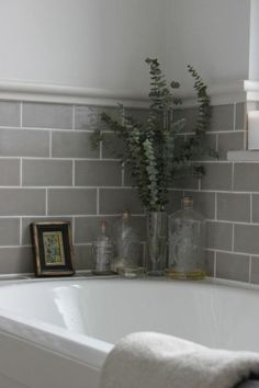Bathrooms Badewanne mit Flaschen als Deko und grauen Fliesen.