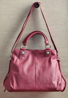 "City Living Purse 46.99 at shopruche.com. This charming burgundy faux leather satchel is a roomy carryall with silver hued hardware, an optional shoulder strap, and a zipper closure.19"" L x 12"" H x 6"" W, -2 interior compartments, -2 interior zipper pockets, -2 interior organizer pouches, -1 exterior zipper pocket"