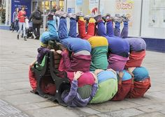 Oct. 24, 2013: Contortionists bend the rules of street performance by squeezing, squishing and squashing themselves into urban spaces in Bangor, Wales. The flexible friends, known as Bodies in Urban Spaces, baffled dog walkers and shoppers by infiltrating window archways, falling under park benches and piling onto roofs.