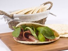 Piadina is a sort of flat bread, originally from Romagna, where it is usually filled with cheese and cured-meat and folded in two or rolled up and eaten like a sandwich.