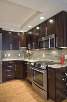 Architectural Ceramics stock glass tile back splash with dark kitchen cabinets. Kitchen by Case Design/Remodeling, Inc.