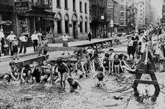 Children on Mulberry St on the Lower East Side turn an excavation site into a temporary swimming hole using water from a fire hydrant as July temperatures hit record heights in the city in 1936
