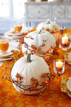 Tischdeko mit weißen Kürbissen und dekorativen orangen Ästen
